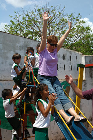Joyce Meyer sliding down a slide with children in Brazil