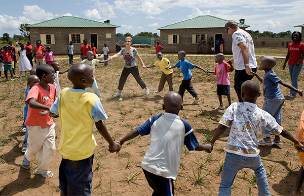 Dave and Joyce spinning in circles with children in Uganda.