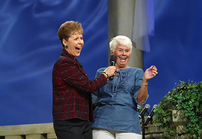 Joyce laughing with a woman on stage