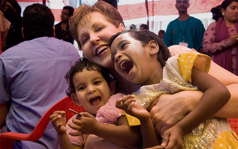 Joyce hugging two girls in India