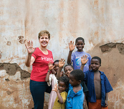 Joyce standing with children from Malawi