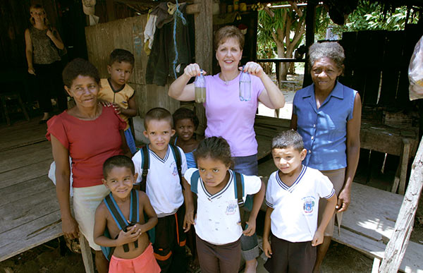 Joyce standing with a group of people showing the before and after on clean water Hand of Hope helped provide.
