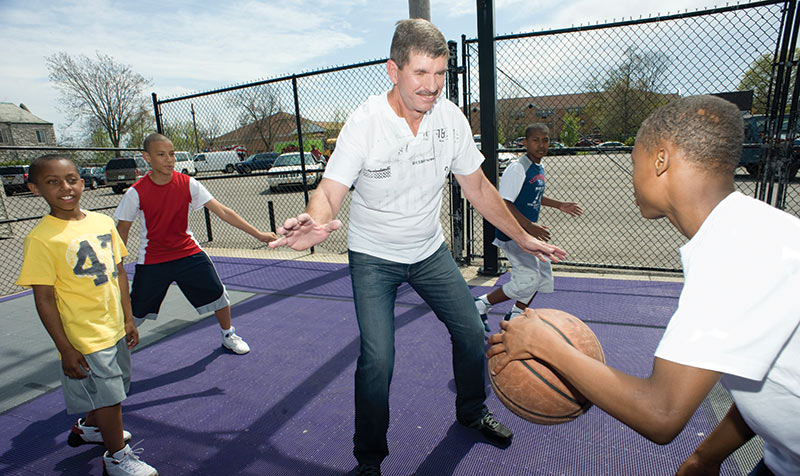 Dave playing basketball with kids at the St. Louis Dream Center