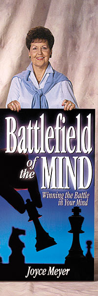 Joyce standing with an oversized version of Battlefield of the Mind